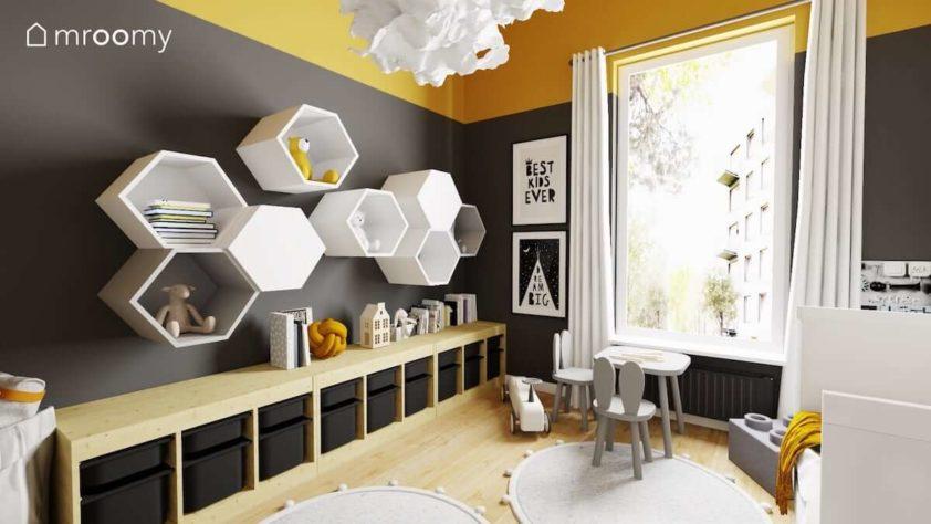 Czarna ściana z heksagonalnymi półkami szary stoliczek z krzesełkami i żółty sufit w pokoju dwóch małych chłopców