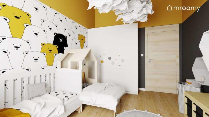 Dwa łóżka na tle tapety w misie szafa z dużymi drewnianymi gałkami i czarno żółte dodatki w pokoju dwójki małych chłopców