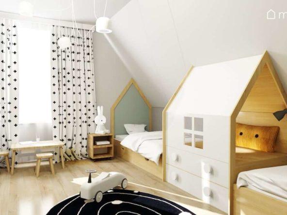 Łóżka z zagłówkami w kształcie domków i kryjówką na środku zasłony w krzyżyki i dywan z motywem w kosmosu w pokoju dwóch przedszkolaków.