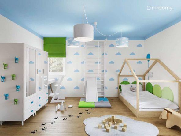 Biały pokój małej dziewczynki z tapetą w chmurki łóżkiem domek i niebieskim sufitem i naklejkami podłogowymi w łapy