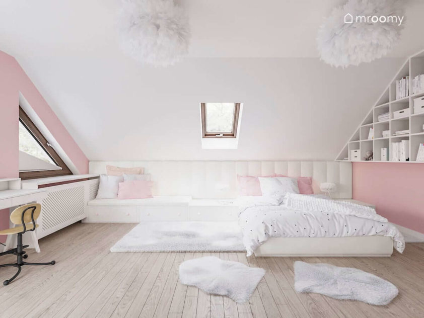 Duże łóżko z tapicerowanym wezgłowiem w biało różowym pokoju ze skosami dla dziewczynki