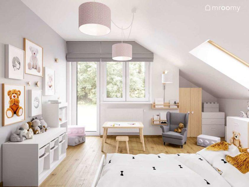 Jasny pokój małej dziewczynki z różowymi akcentami w którym jest szary fotel uszak i stoliczek z krzesłem wraz z misiami