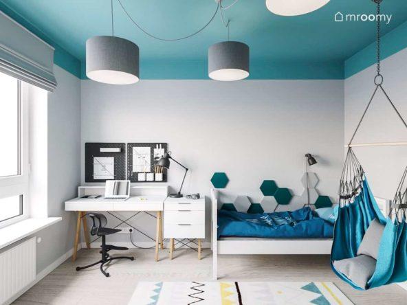 Pokój dziewczynki z wiszącym fotelem i turkusowym sufitem zawierający proste białe biurko i łóżko