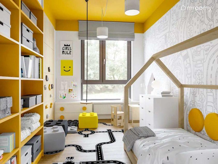 Łóżko domek huśtawka żółte regały i tapeta w miasto i ulice w pokoju dla małego dziecka z żółtym sufitem