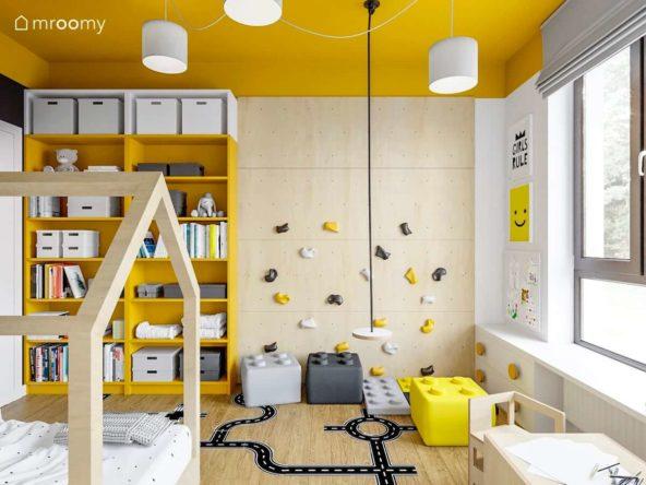 Huśtawka i ścianka wspinaczkowa obok żółtych regałów w pokoju małej dziewczynki