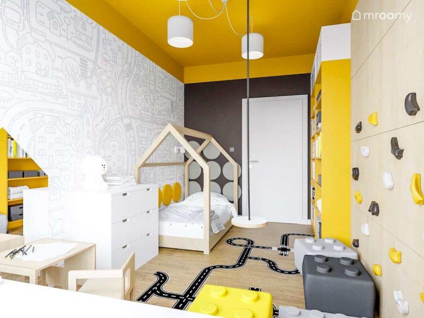Łóżko domek przy ścianie z czarno-białą tapetą w miasto i ulice w pokoju małej dziewczynki  w którym są również ścianka wspinaczkowa i żółto-białe meble