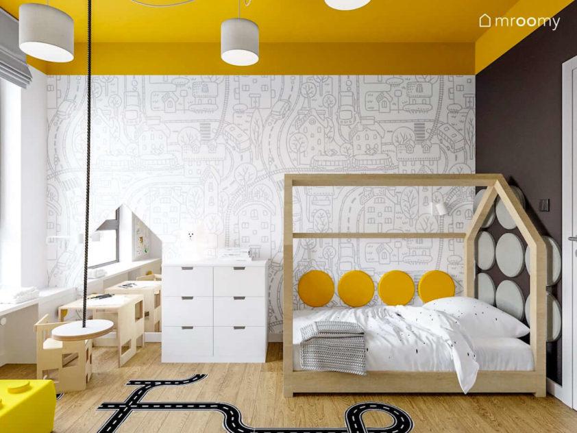 Huśtawka łóżko domek z miękkimi panelami na ścianie z tapetą w ulice obok stojące krzesełko ze stoliczkiem i biały regał w pokoju dziewczynki kochającej auta.