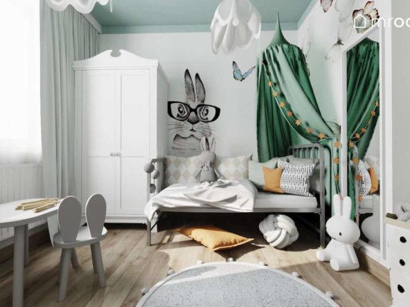 Metalowe łóżko z zielonym baldachimem stolik z krzesełkiem biała szafa i tapeta z królikiem w pokoju małej dziewczynki