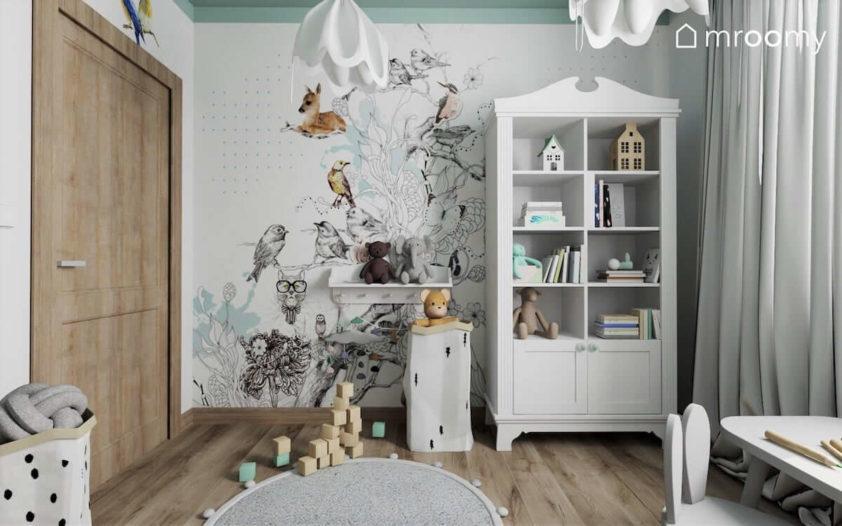Biała komoda na tle tapety z bajkowym drzewem i zwierzątkami i miętowym sufitem w pokoju małej przedszkolnej dziewczynki