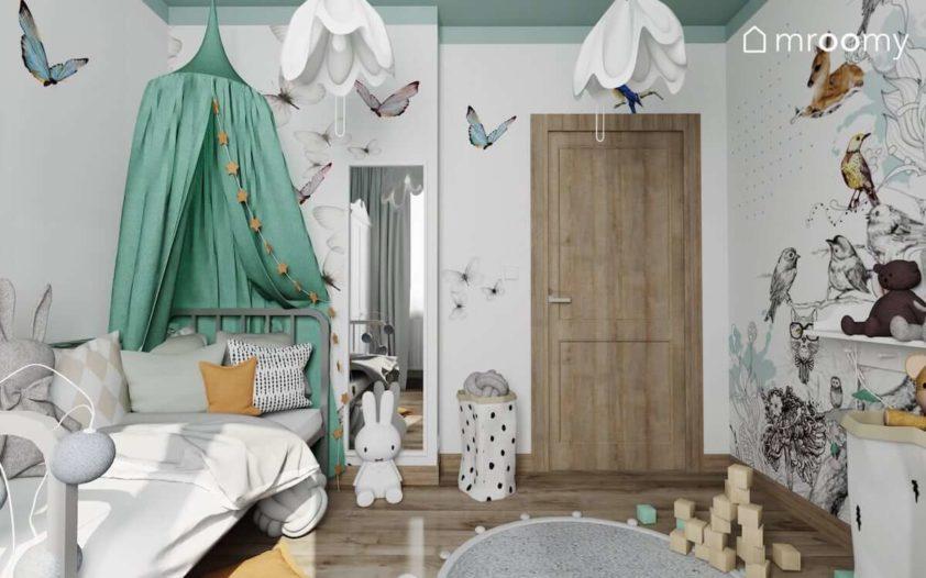 Łóżko z miętowym baldachimem tapeta w motyle i lampka królik w małym pokoju dziewczynki