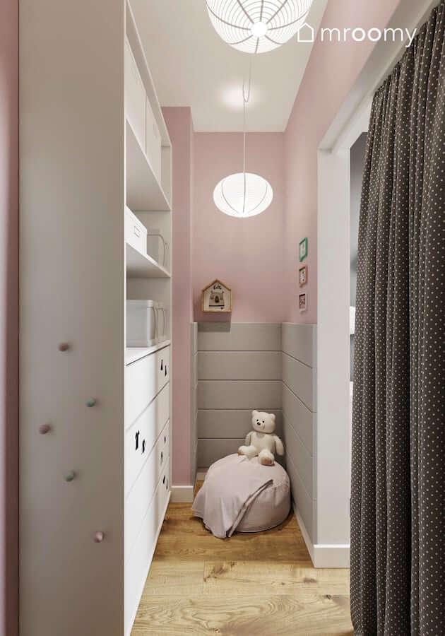 Szare panele ścienne i białe szafy w garderobie w odcieniach różu przy pokoju dziewczynki