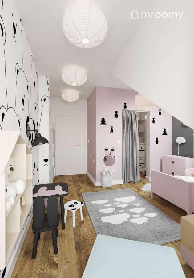 Stolikiem i krzesełko dziecięce z motywem królika oświetla kinkiet zamontowany na uchu pandy z tapety w pokoju dziewczynki z różowymi ścianami
