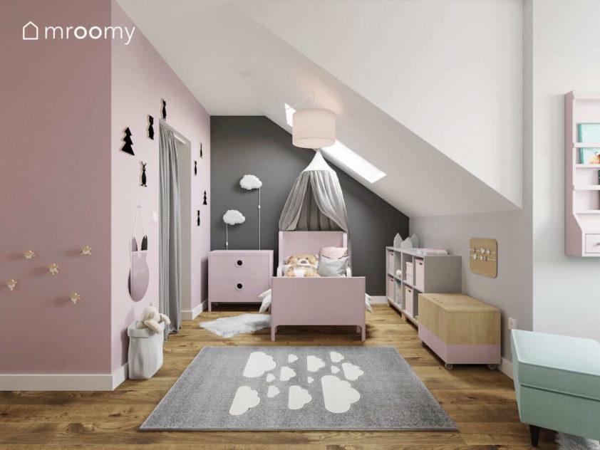 Różowe łóżko z baldachimem i z komodą na tle szarej ściany obok różowej garderoby w pokoju dziewczynki.