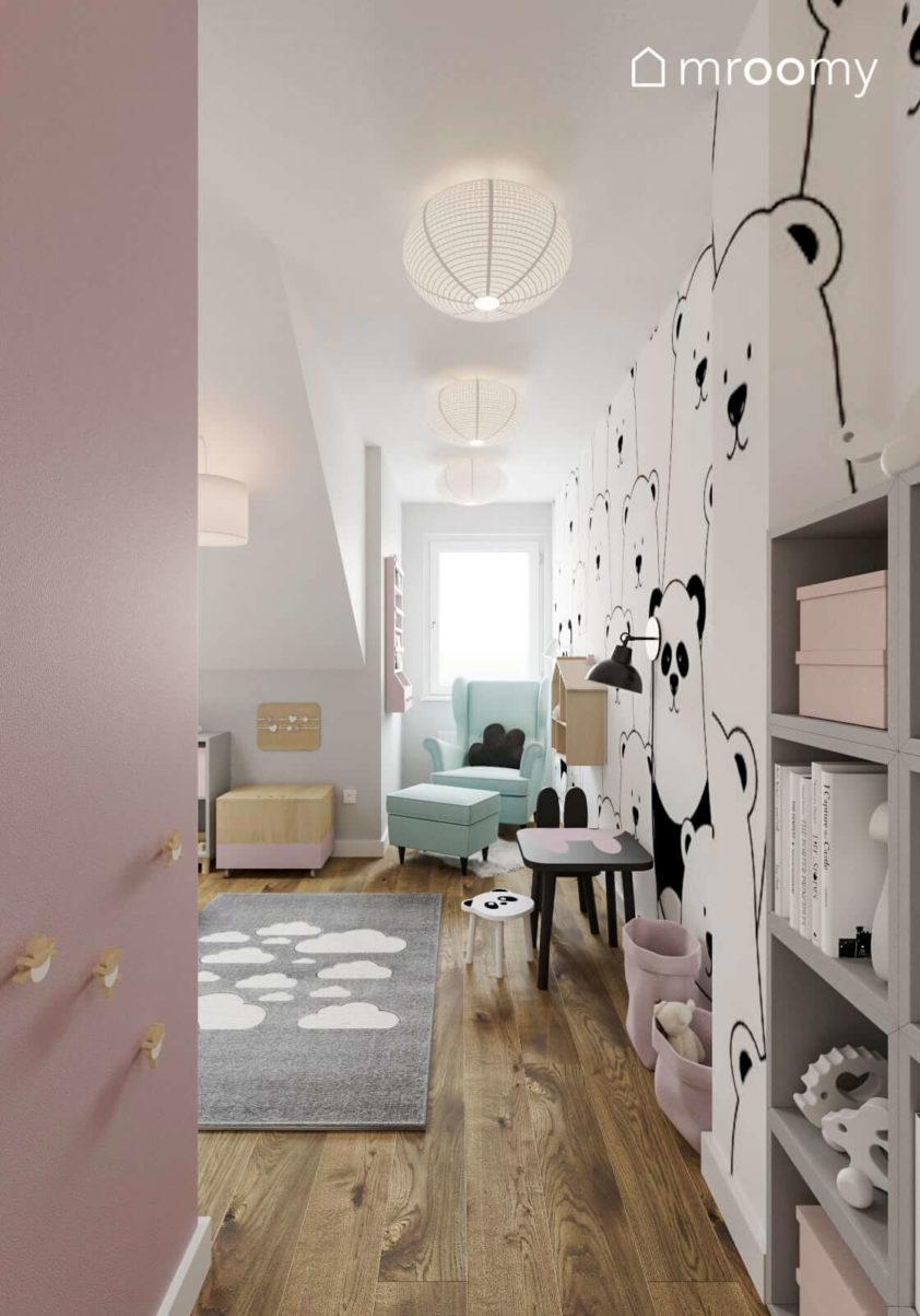 Seledynowy fotel do czytania tapeta w pandy i stoliczek do rysowania w poddaszowym pokoju małej dziewczynki