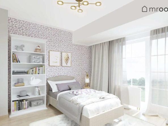 Duże tapicerowane łóżko z klasycznym zagłówkiem biały regał i tapeta w fioletowe liście w jasnym pokoju ośmioletniej dziewczynki