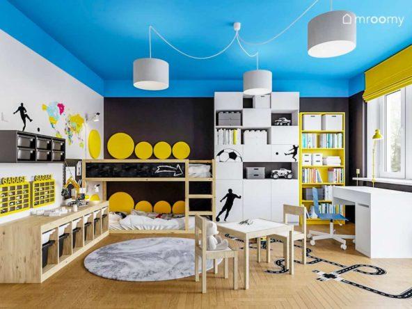 Piętrowe łóżko czarna ściana i niebieski sufit w pokoju dwóch chłopców fanów piłki nożnej
