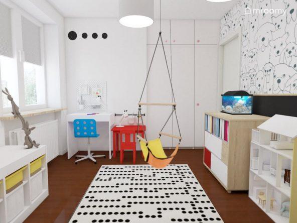Biurko i stoliczek  w jasnym pokoju rodzeństwa w którym znajduje się kolorowa huśtawka i dywan w kropki