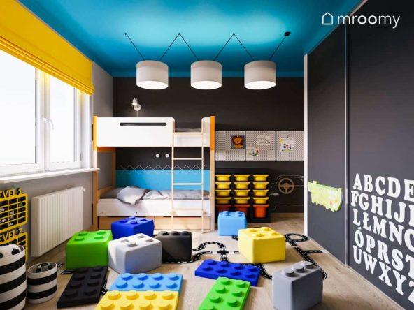 PIętrowe łóżko w czarno-niebiesko-żółtym pokoju dwójki małych dzieci z miękkimi pufami w kształcie lego i niebieskim sufitem
