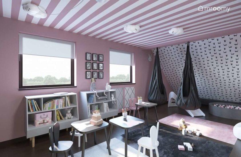 Miejsce do zabawy ze stoliczkami i krzesełkami w królicze uszy w poddaszowym pokoju dla dwóch małych dziewczynek z różowymi pasami na suficie i różowymi ścianami