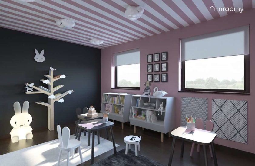 Regał-drzewko półki na książki drewniane dziecięce krzesełka i stoliczek w pokoju dla małych dziewczynek z szarą ścianą i różową tapetą