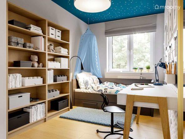Pokój dla dziewczynki z niebieskim sufitem i fluorescencyjnymi gwiazdkami baldachimem nad łóżkiem i meblami z drewna