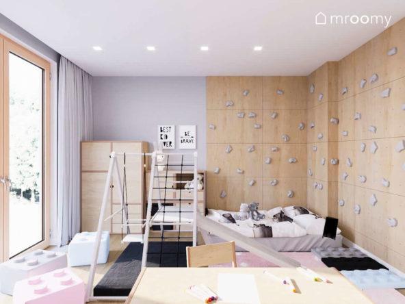 Miejsce do spania obok ścianki wspinaczkowej w pokoju dla małej dziewczynki z szarą ścianą i różowymi dodatkami