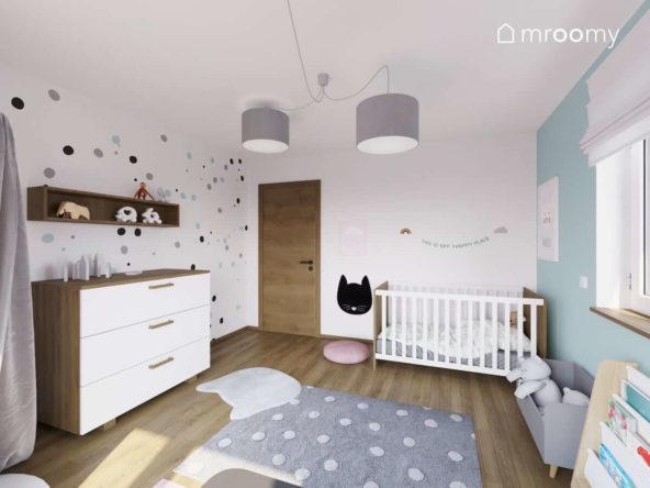 Pokój małej dziewczynki z łóżkiem komodą dywanem w kropki i tapetą w kropki
