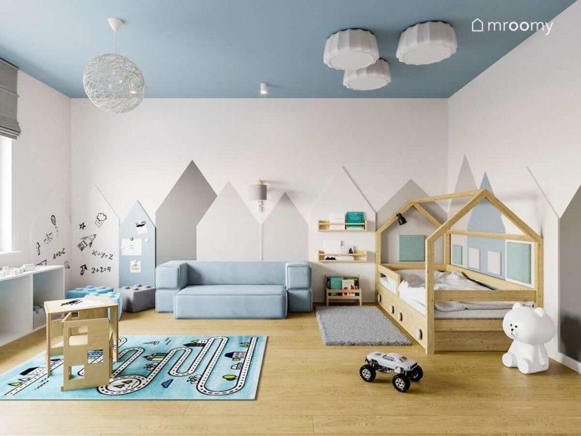 Pokój przedszkolaka z łóżkiem-domkiem sofą dywanem z drogą i okładzinami drewnianymi na ścianie