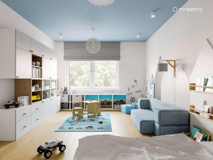 Pokój małego chłopca z niebieskim sufitem stoliczkiem z krzesełkami białą szafą i niebieską sofą