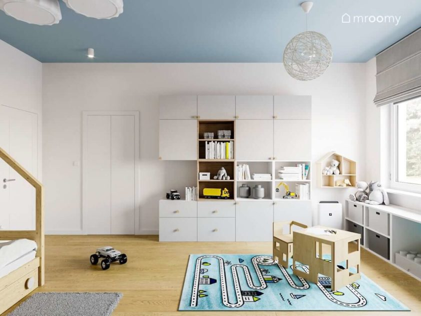 Krzesło i stolik dziecięcy w pokoju małego przedszkolaka chłopca z białą szafą i niebieskim dywanem z motywem drogi