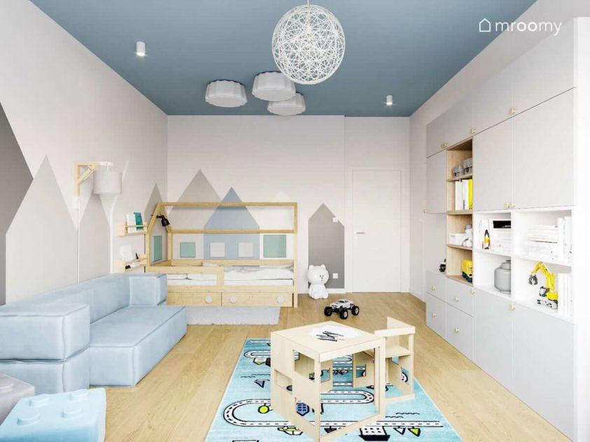 Kącik do spania dla chłopca z łóżkiem domkiem stoliczkiem krzesełkami i domkami na jasnej ścianie