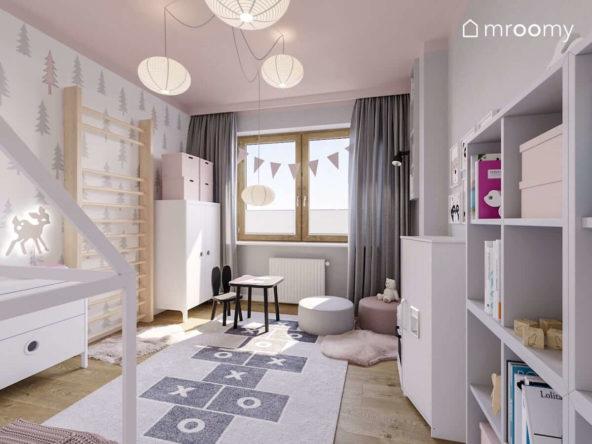 Białe meble drabinka różowy sufit i czarne krzesełko ze stoliczkiem w pokoju małej dziewczynki