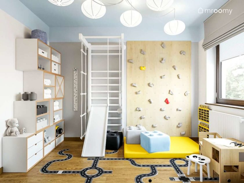 Kącik ze ścianką wspinaczkową i białą drabinką obok regałów modułowych z białej sklejki w pokoju małego rodzeństwa chłopca i dziewczynki