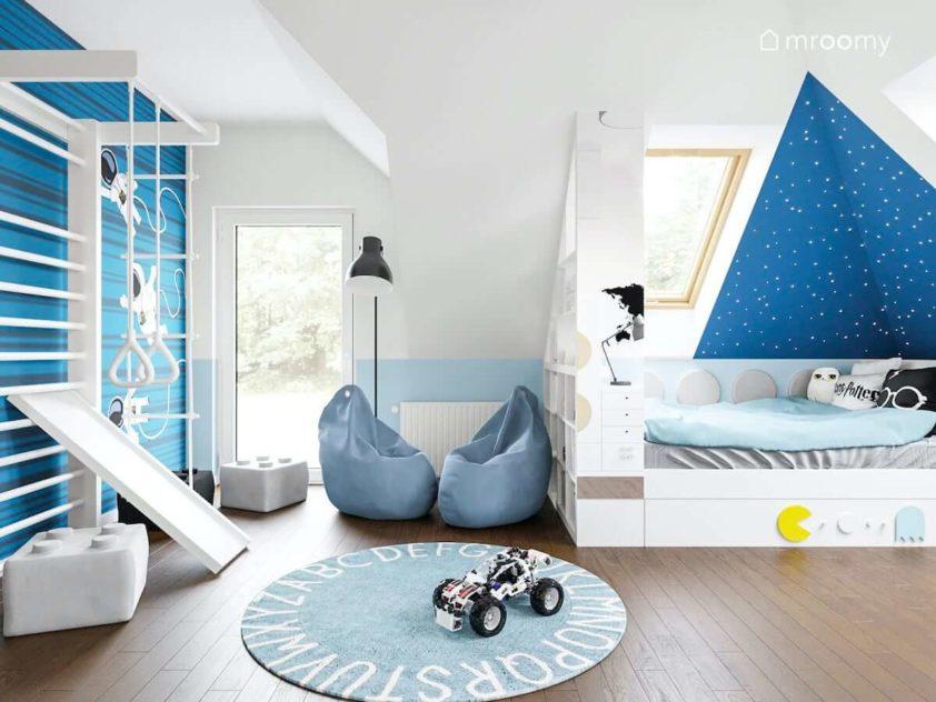 Biała drabinka gimnastyczna przy niebieskiej ścianie worki sako okrągły dywan i łóżko przy ścianie ze skosem w pokoju chłopca