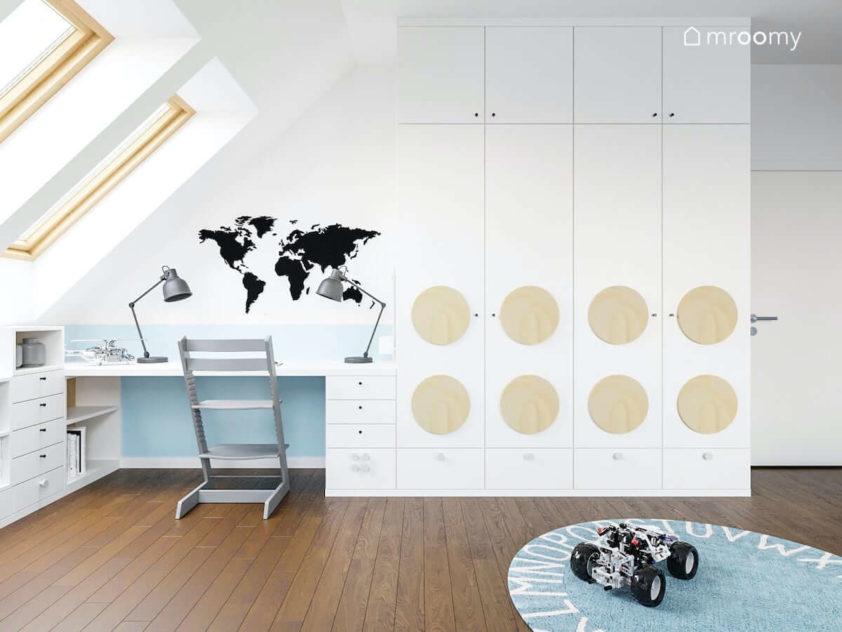 Biurko przy ścianie ze skosem w pokoju chłopca nad którym jest naklejka z mapą świata obok biała szafa z okrągłymi panelami