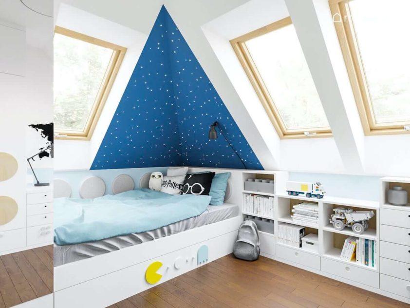 Łóżko przy niebieskiej ścianie z gwiazdkami w pokoju małego chłopca obok regału wykonywanego na zamówienie