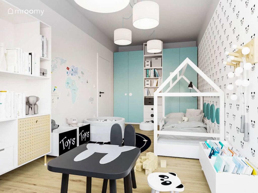 Pokój małego dziecka chłopca lub dziewczynki z łóżkiem domkiem czarnym stolikiem królikiem i dużą szafą z turkusowymi frontami