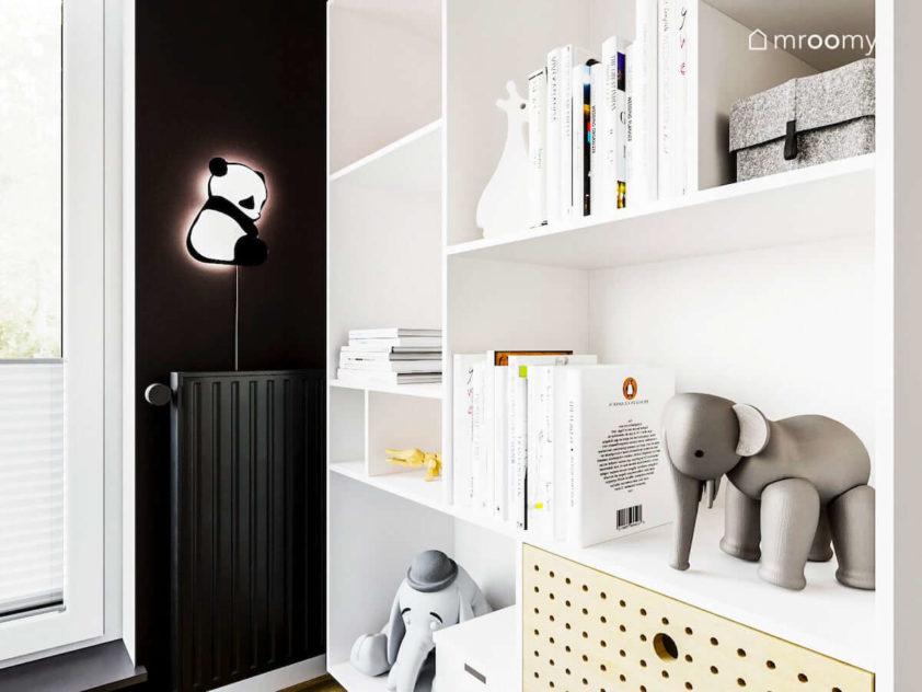 Kawałek czarnej ściany z lampką panda obok białego regału w pokoju małego dziecka