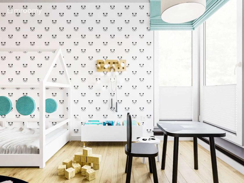 Łózko domek półka na książki czarny stoliczek z motywem królika i tapeta w pandy w pokoju małej dziewczynki