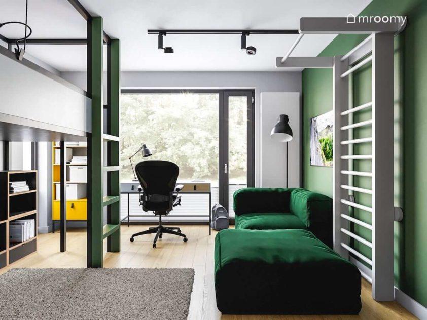 Zielona sofa biurko wygodny fotel przy oknie i drabinka gimnastyczna w pokoju nastolatka