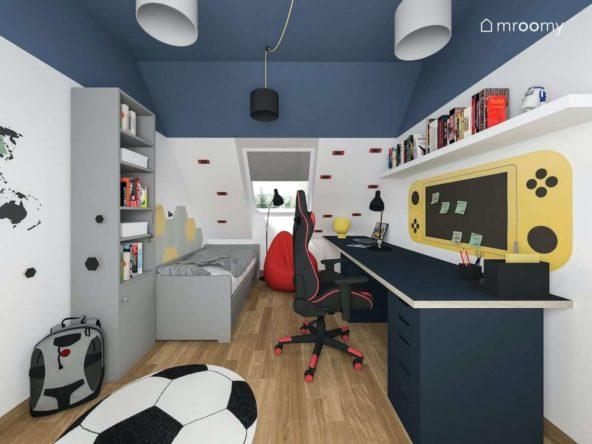 Poddaszowy pokój dla nastolatka z gamingowym fotelem szarymi meblami i granatowym sufitem