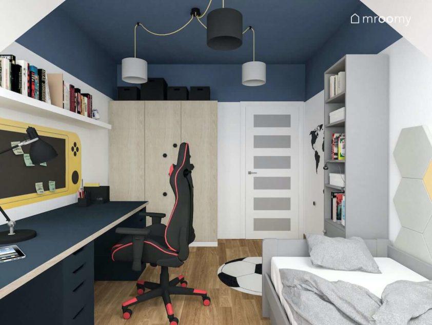 Szare łózko i regał na książki granatowe biurko szafa w okleinie drewnianej i gamingowy fotel w niewielkim pokoju dla nastolatka