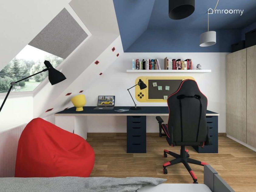 Duże biurko dla nastolatka grającego w gry komputerowe z gamingowym fotelem obok którego jest czerwony worek sako