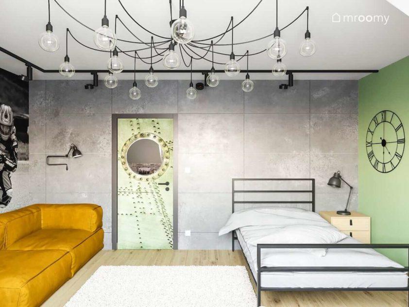 Betonowe ściany w pokoju nastolatka gdzie znajduje się żółta miękka sofa i metalowe łóżko