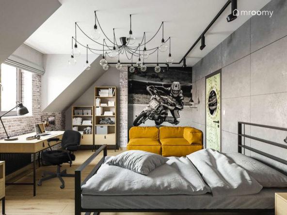 Duży pokój na poddaszu dla nastolatka który interesuje się motocyklami w stylistyce loftowej z kanapą metalowym łóżkiem biurkiem i dużą lampą