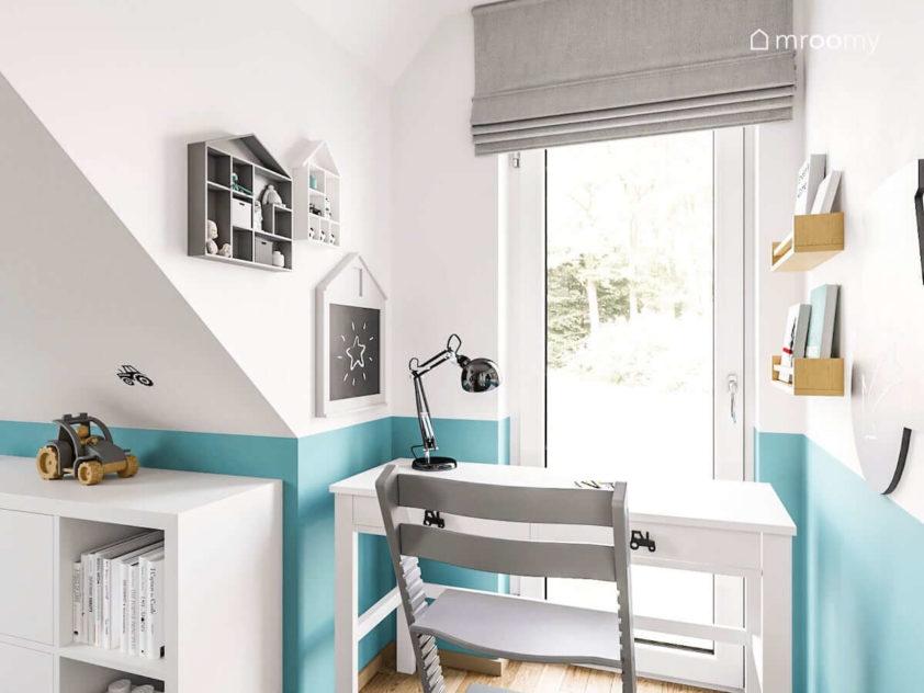 Białe biurko przy oknie z szarą roletą rzymską i turkusowym kolorem na ścianie w pokoju dla chłopca