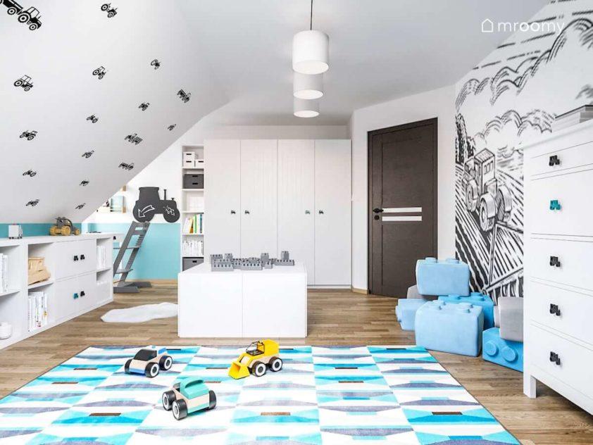 Niebieski dywan we wzorki i ściany w naklejki traktorki w pokoju małego chłopca z białymi meblami