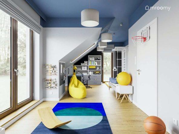 Pokój dziecka ze skosem utrzymany w niebiesko-żółtej tonacji z workiem sako  i białą drabinką do ćwiczeń