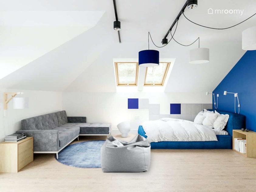 Miękkie duże tapicerowane niebieskie łóżko szafa sofa fotel sako i panele ścienne w pokoju nastolatka na poddaszu