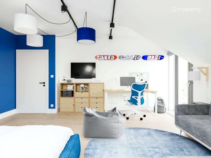 Miejsce do nauki w pokoju nastolatka obok regał modułowy ze sklejki niebieskie abażury i duży szary dywan